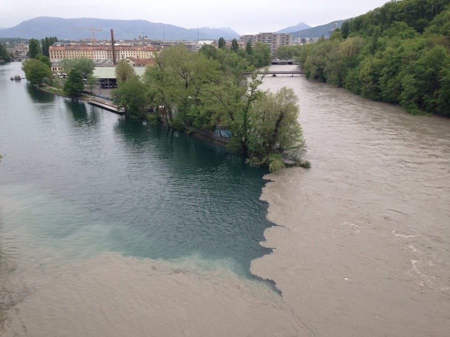 The muddy water of the Arve pushing into the the far side of the Rhone River.